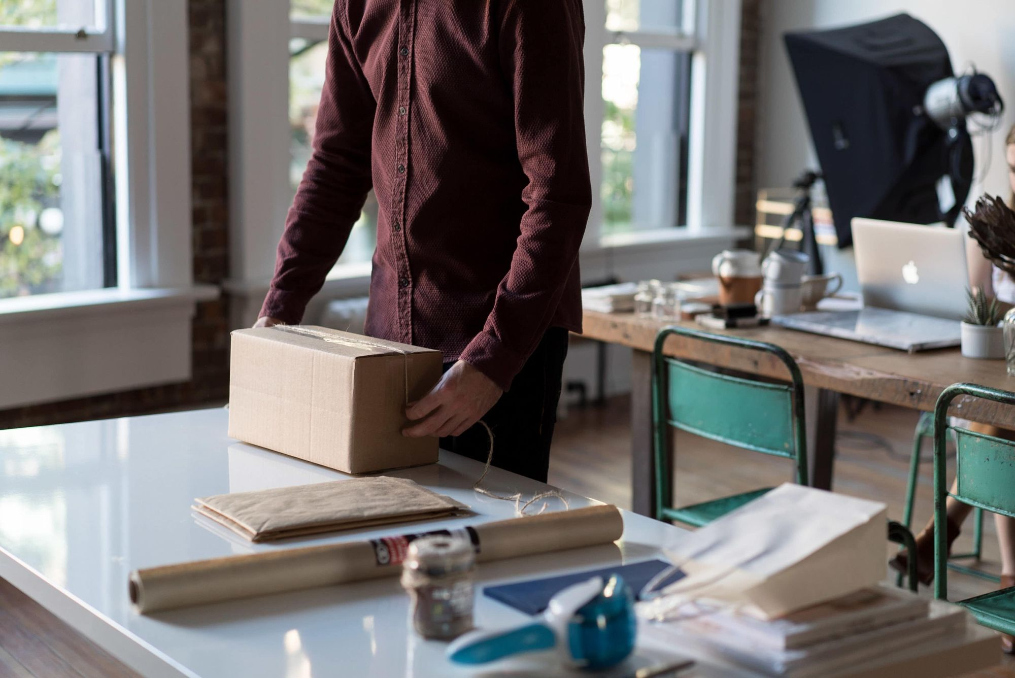 Man prepares box that would be an ideal example for how to save money on USPS shipping